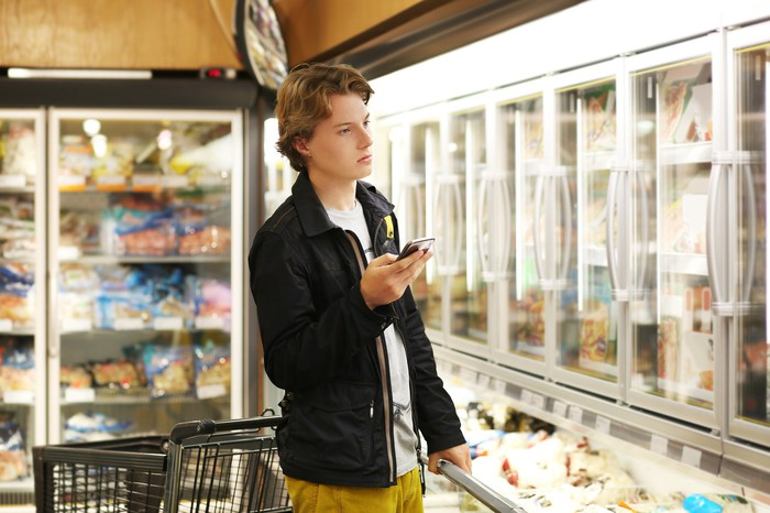 A young man checks his smartphone as he shops for groceries.
