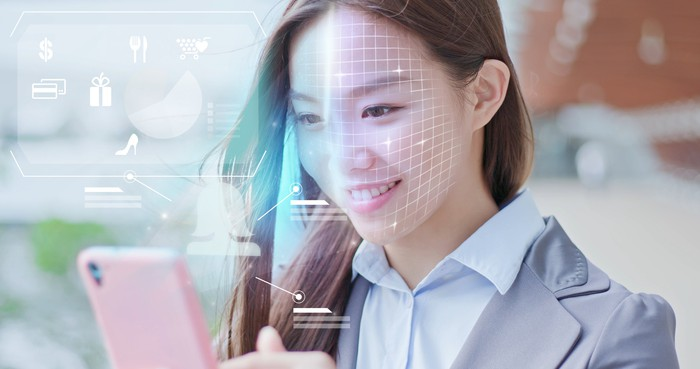 A woman uses a facial-recognition app on her smartphone.