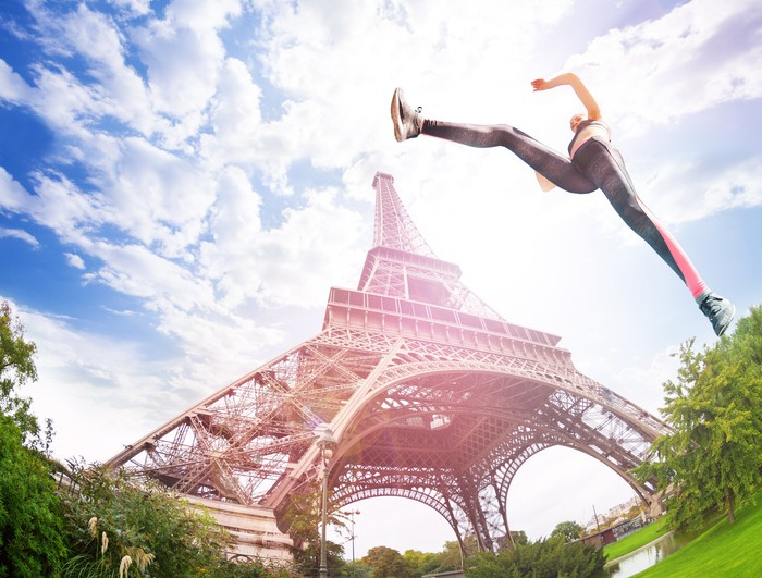 A woman in athletic clothing leaping in the air in front of the Eiffel Tower in Paris.