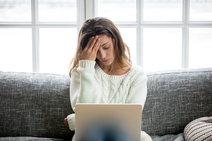 Woman sitting on couch in front of laptop, holding her head as if stressed
