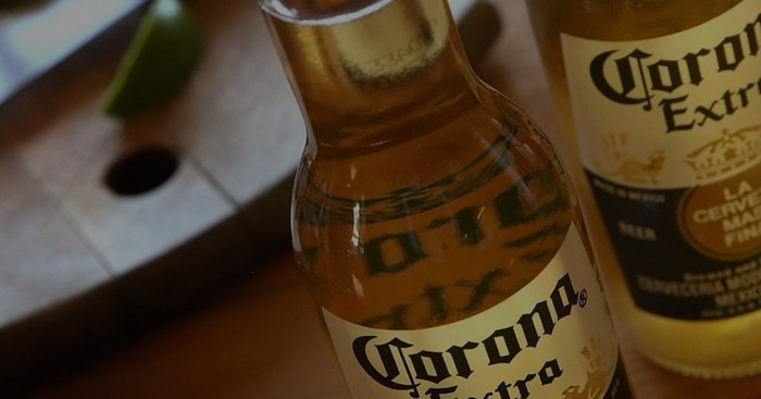 Two Corona Extra beer bottles with out-of-focus background.
