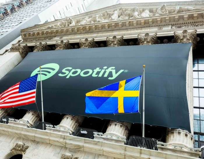 Spotify banner on the NYSE building; American and Swedish flags are in front.