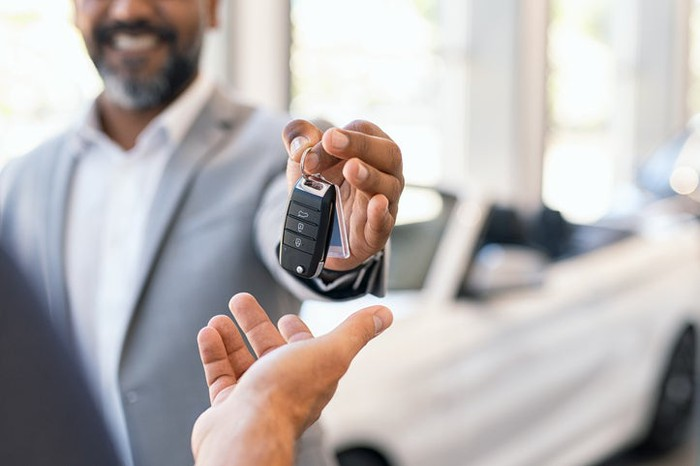 A salesman handing new car keys to a customer.