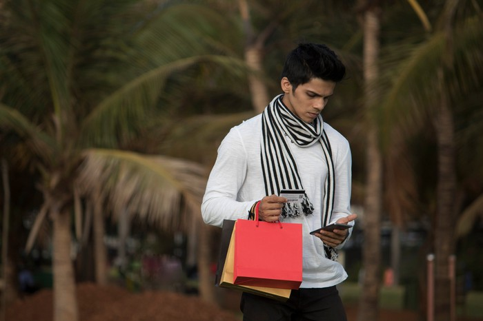 A young man with red and yellow bags in one hand looks down at his phone in the other.
