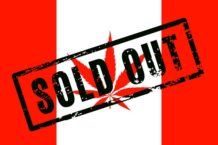 """A Canadian flag with a cannabis leaf in place of the red maple leaf, and the words """"Sold Out"""" stamped across the flag."""