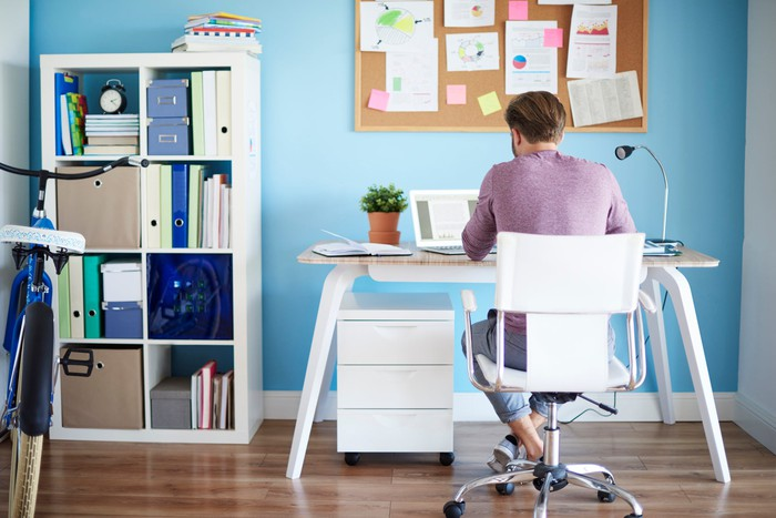 Man siting at desk in home office, facing a blue wall with a memo board