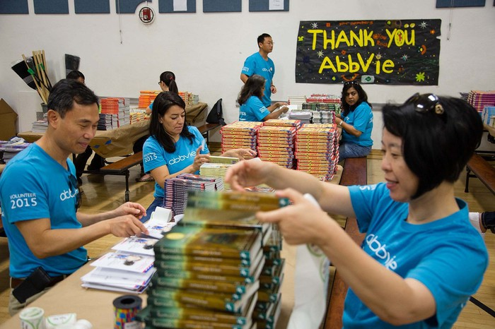 Five people wearing AbbVie t-shirts with books in a room with a thank-you poster in the background.