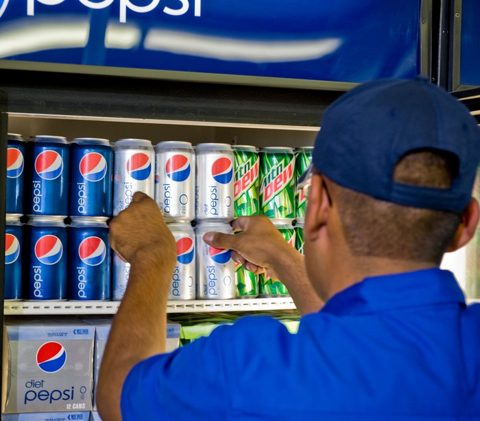 A Pepsi worker stocking a cooler.