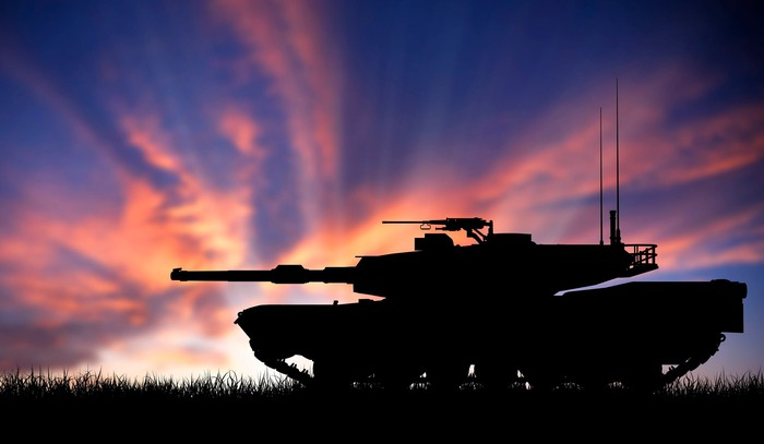 A tank silhouetted against a sunset.