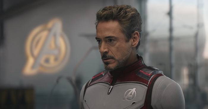 Iron Man stands near a lighted Avengers emblem, looking concerned.