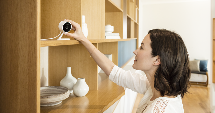 Woman setting up Amazon Cloud Cam on a shelving unit