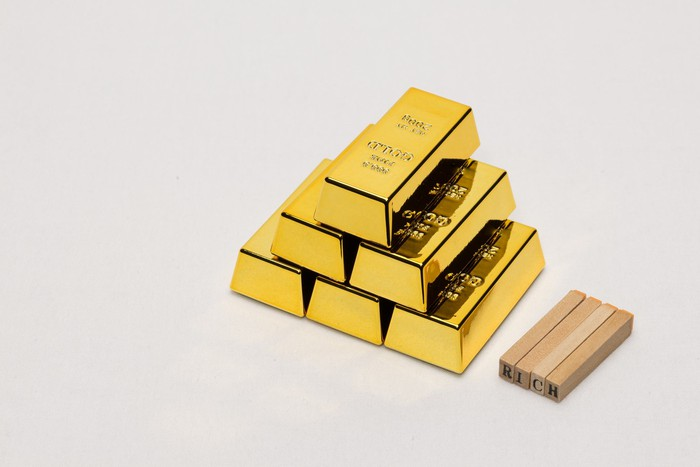 Gold bars stacked in a pyramid shape - 3-2-1. They have indistinguishable writing on them and are placed in an off-white background with a handful of small pieces of wood next to them.