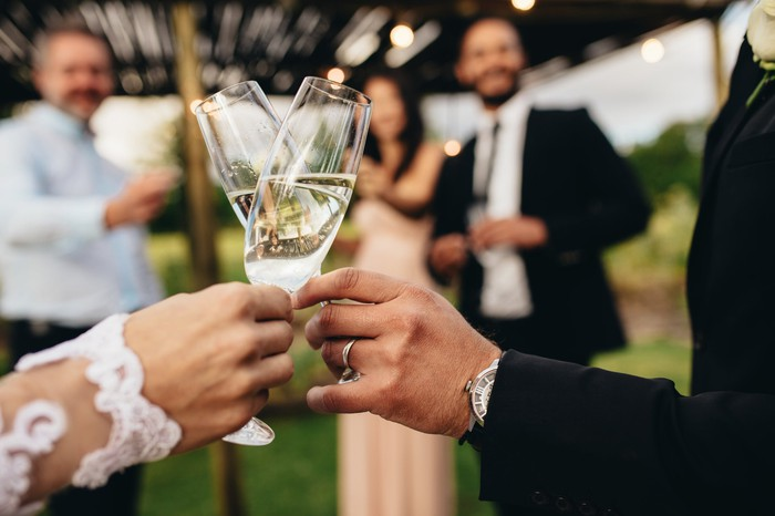 A couple clinking champagne glasses at their wedding reception.