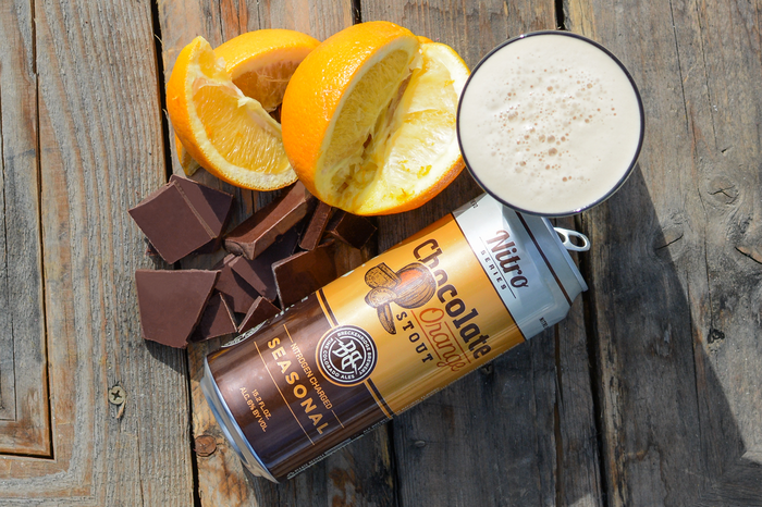 A can of chocolate orange stout beer with orange slices and pieces of chocolate, all set on a wooden surface.