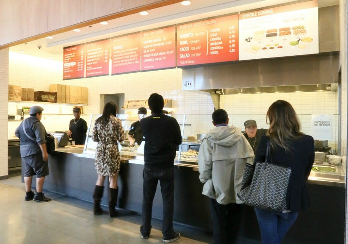 People wait in line at a Chipotle.