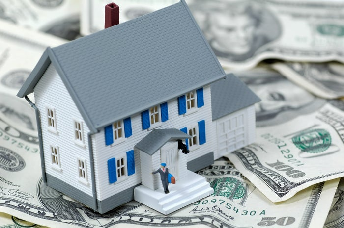 A model house is shown, sitting on a bunch of paper U.S. currency