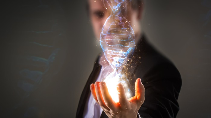 Man in a suit with a 3D holographic image of a DNA strand being projected from his open, outstretched hand.