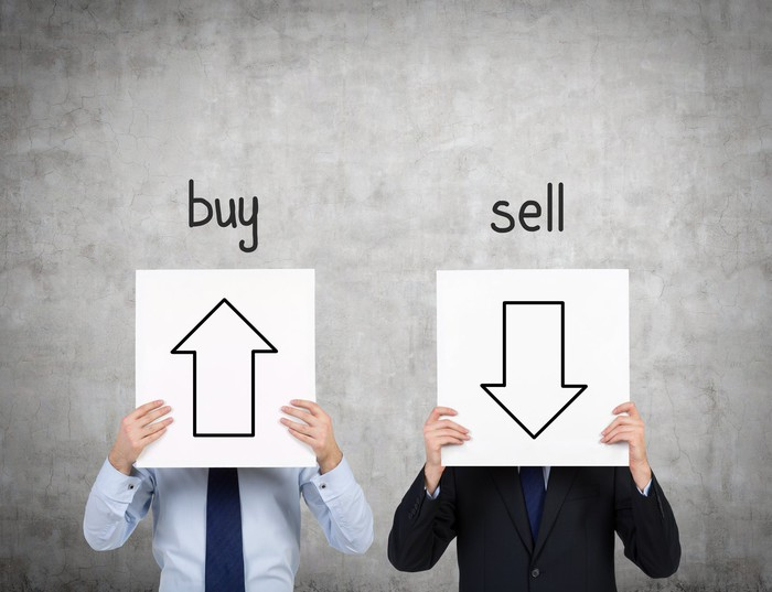 A man holding a sign with an arrow pointing up in front of his face with the word buy over it and another man holding a sign with an arrow pointing down in front of his face with the word sell over it