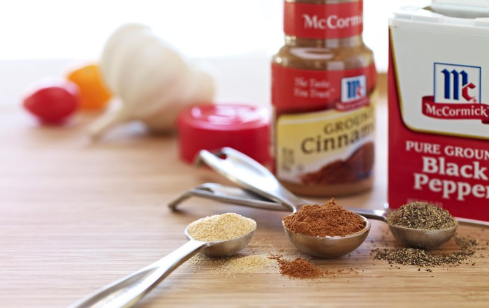 Two jars of McCormick brand cinnamon and black pepper on a wood table, with spoons full of various spices and some raw herbs.