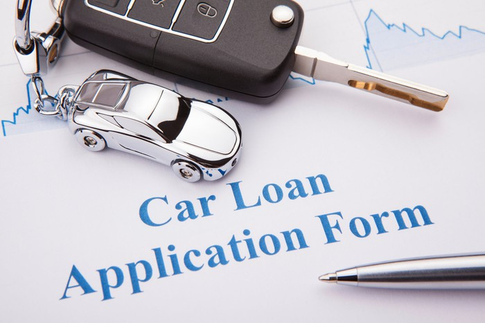 "Paper reading ""Car loan application form"" with pen and key sitting on top."