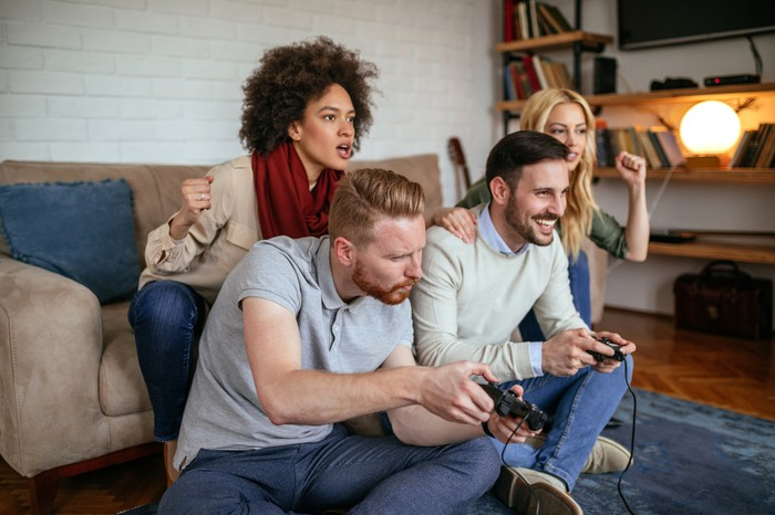 Two young men playing video games while two young women cheer them on.