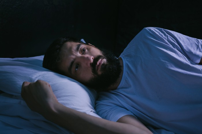 Man with eyes open lying in bed in dark room