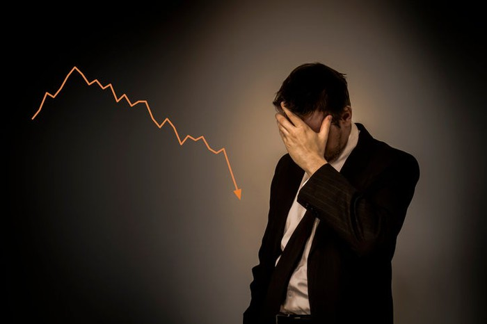 A man holding his head in his hand stands next to a declining chart.