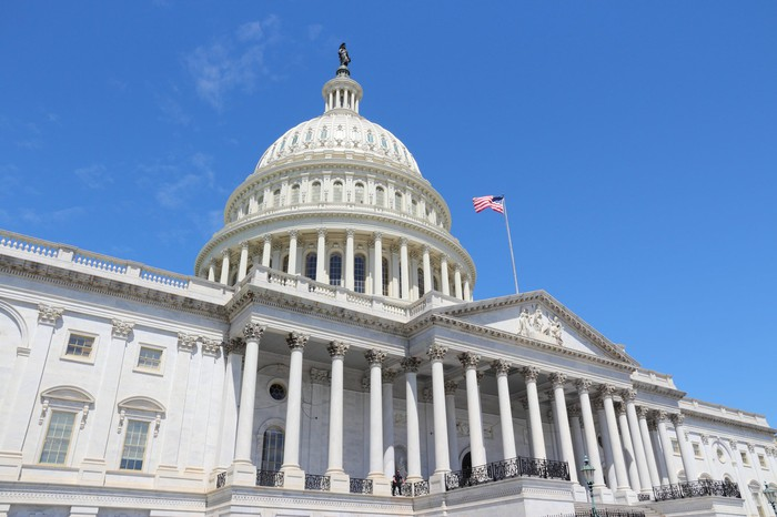 U.S. Capitol building under a mostly cloudless blue sky.