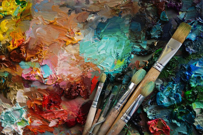 Various colored paints on a canvas with several paintbrushes on top of it.