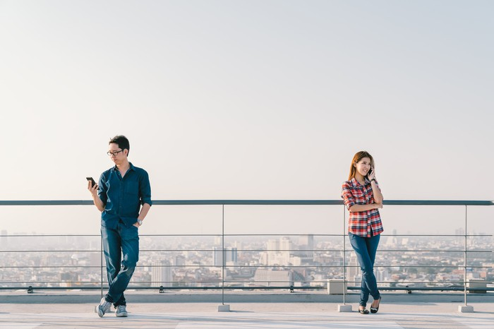Young man and woman standing far apart using smartphones on a building roof.