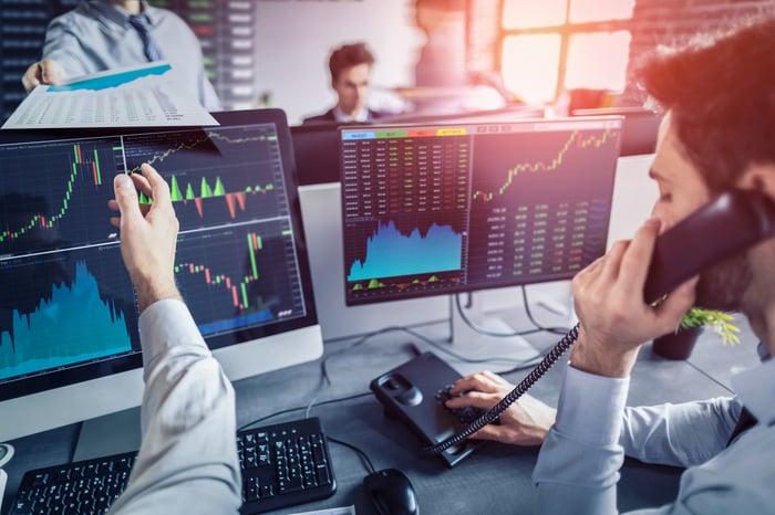 Wall Street traders looking at stock screens.