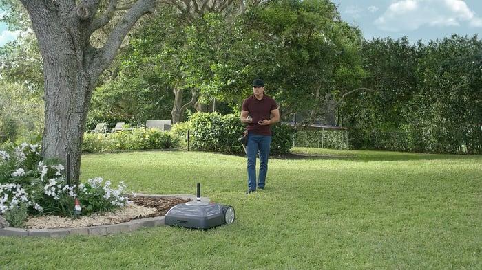 Man watching his iRobot Terra mower in the yard.