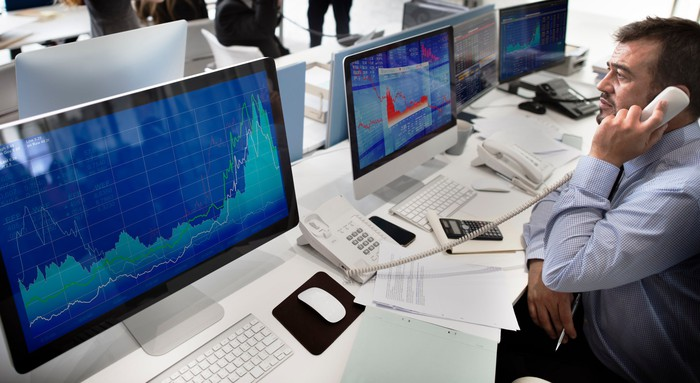 A professional stock trader talking on the phone while looking at stock charts on the monitor screens in front of him.