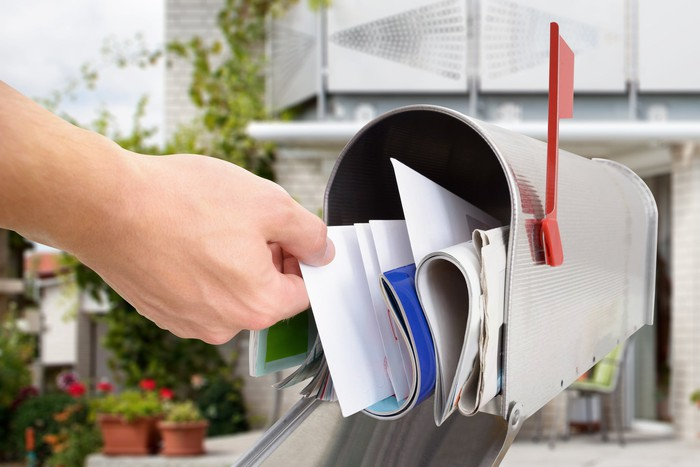 A hand reaches into a mailbox full of mail.