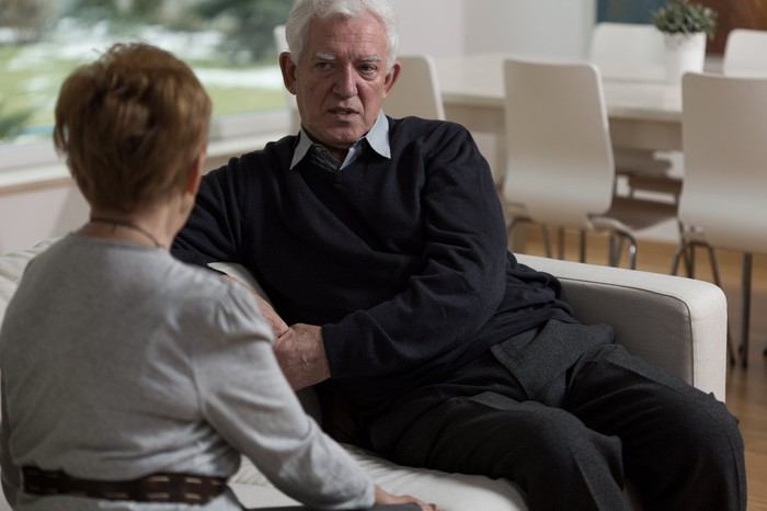 Older man with serious expression sitting across from woman on couch.