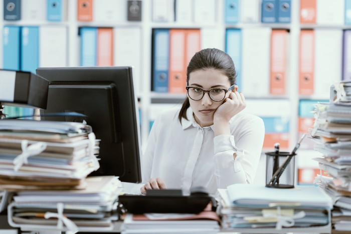 Frowning woman at desk loaded with file folders