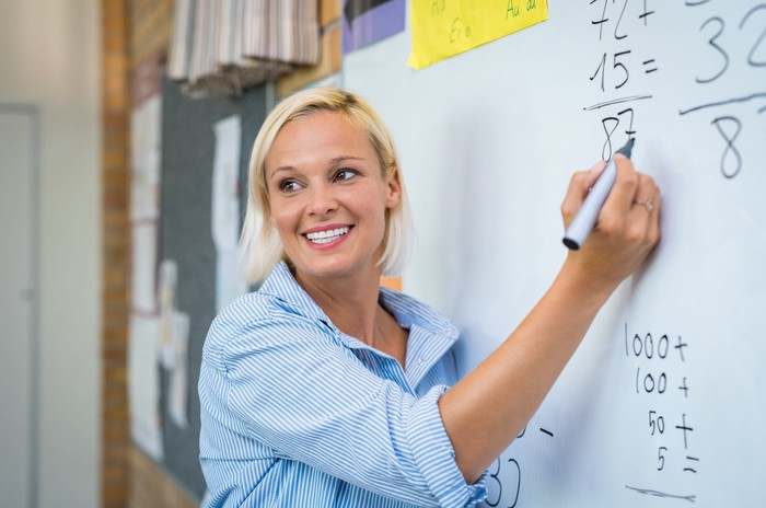 Smiling woman doing math on whiteboard