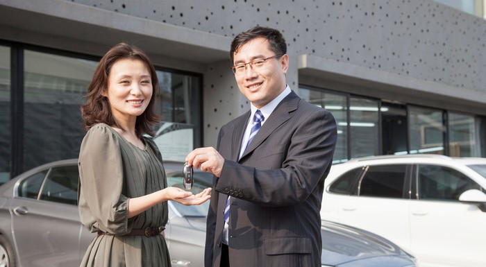 A male auto dealer handing a female customer the keys to a car.