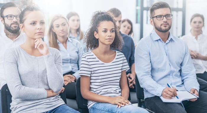A small business team listens to a seminar presentation.