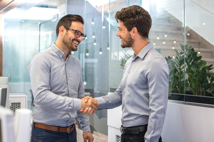 Two men in collared shirts shaking hands