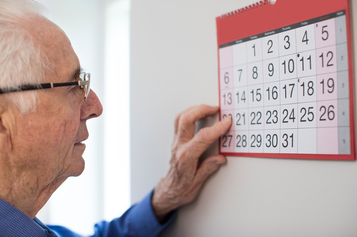 Older man looking at a wall calendar