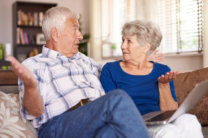 Senior couple using laptop on couch and holding arms up as if confused