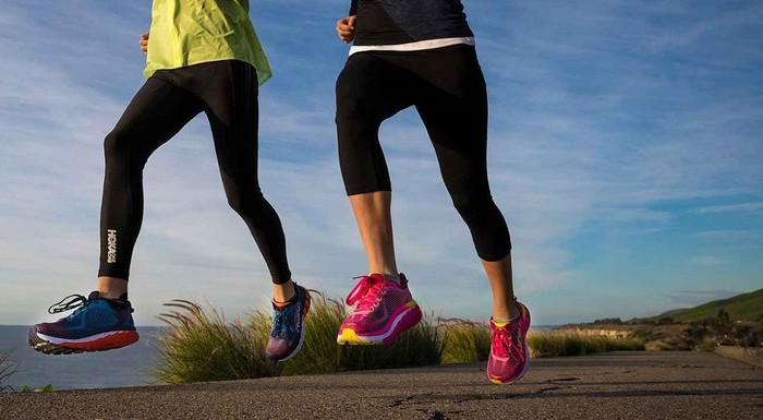 Two women running while wearing colorful Deckers shoes.
