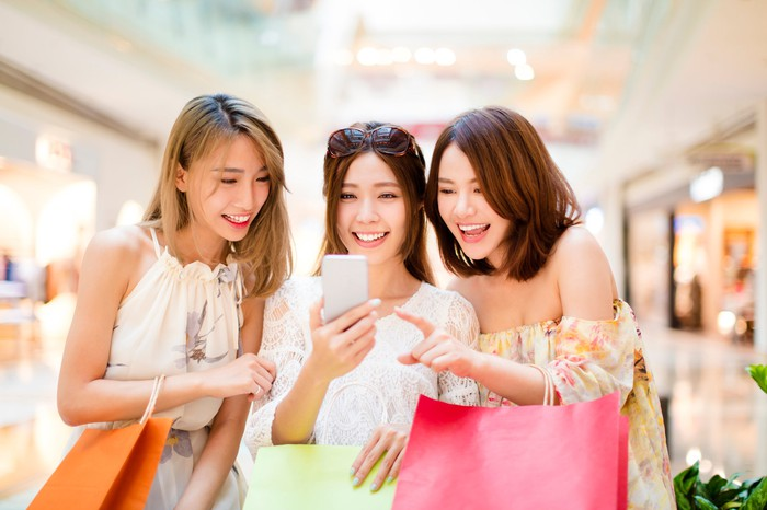 Three young women check a smartphone while shopping.