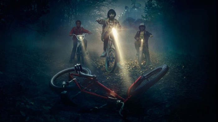 Three boys on bicycles shining lights on a downed bicycle, from the first season of Stranger Things.
