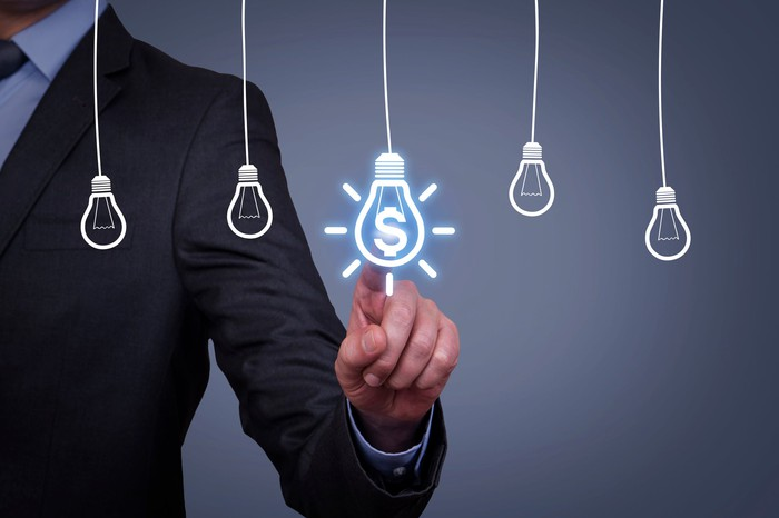 Person in suit pointing to image of light bulb with a glowing dollar sign in it next to other light bulbs without dollar signs.
