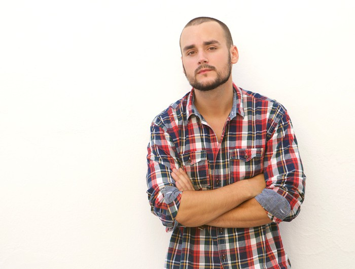 Young man in plaid shirt standing with arms crossed