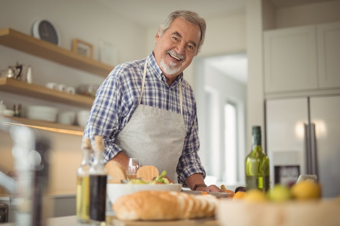 Smiling senior man wearing an apron and standing in front of a kitchen counter with olive oil, bread, and a salad on top of it.