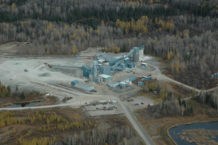Mining complex amid a landscape of forest and subarctic grassland.