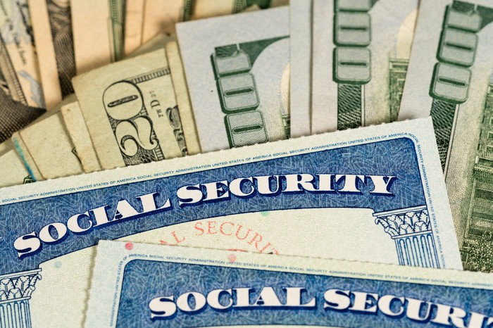 Two Social Security cards lying atop large fanned stacks of cash.